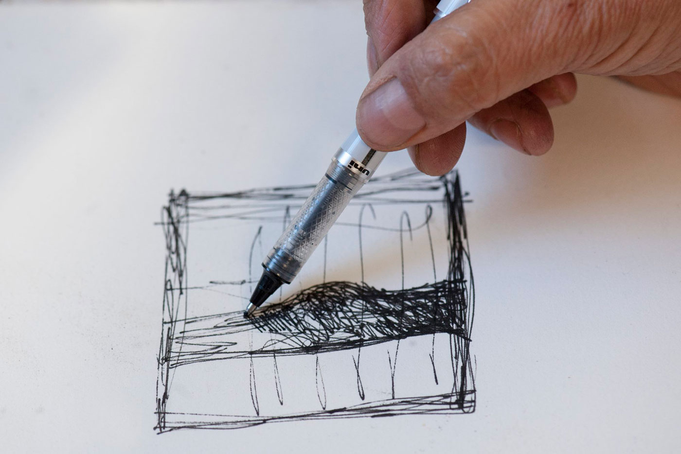 A close up on a person's hand.  The hand is holding a pen in the middle of a sketch. - click to view larger image