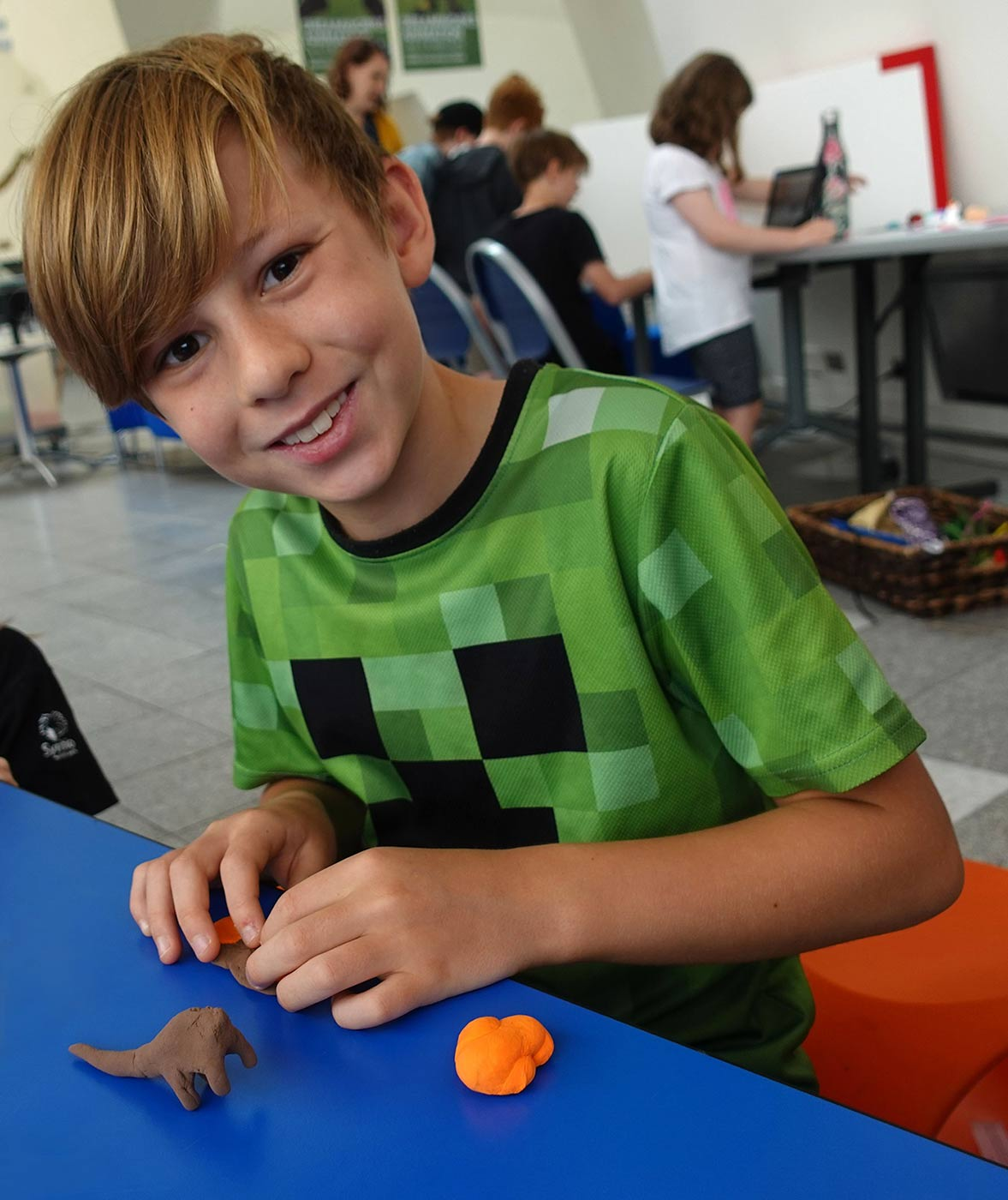 A young boy is smiling for the camera while participating in a craft activity at the National Museum of Australia.