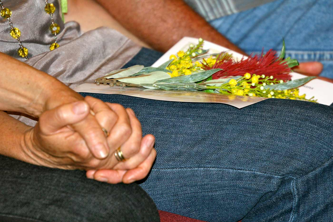 Colour photograph showing a close-up view of clasped hands and a spray of wattle and bottlebrush flowers resting on a person's lap. - click to view larger image