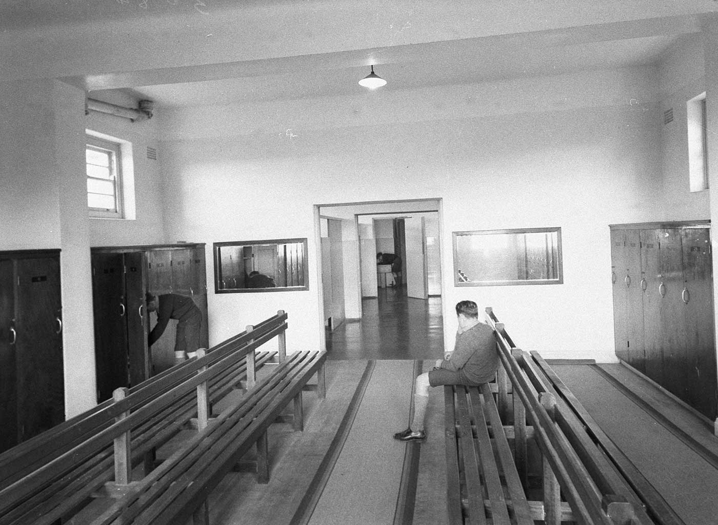 Black and white photo showing a room with wooden lockers lining the walls and two sets of long wooden benches at the centre. A boy in school uniform sits with his back to the camera, tying a shoelace, another boy leans into a locker and, at the far end of the room, a third boy leans over a sink.