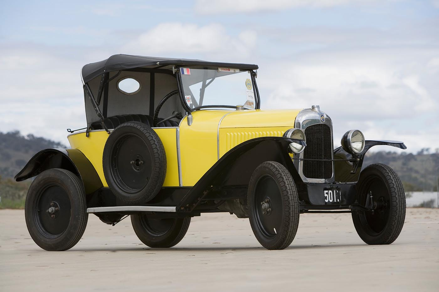 A vintage car with yellow and black features including a soft-top. - click to view larger image