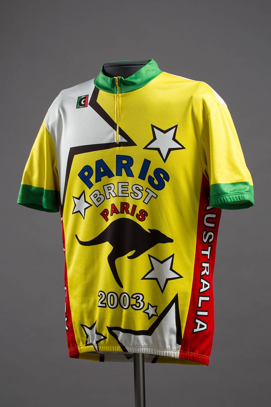 A cycling jersey which consists of a quarter zip t-shirt that is yellow down the front. The t-shirt has a green collar with green and yellow sleeves. Down the left and right side of the t-shirt is a red stripe with 'AUSTRALIA' printed in black and white within the stripe. Featured across the front of the t-shirt are various white stars, a black outline of a kangaroo and text that reads 'PARIS / BREST / PARIS / 2003'. The text is blue, white, and red in colour. The front right side of the t-shirt has a 'GIRAMONDO' logo that is green, white, red and black in colour. - click to view larger image