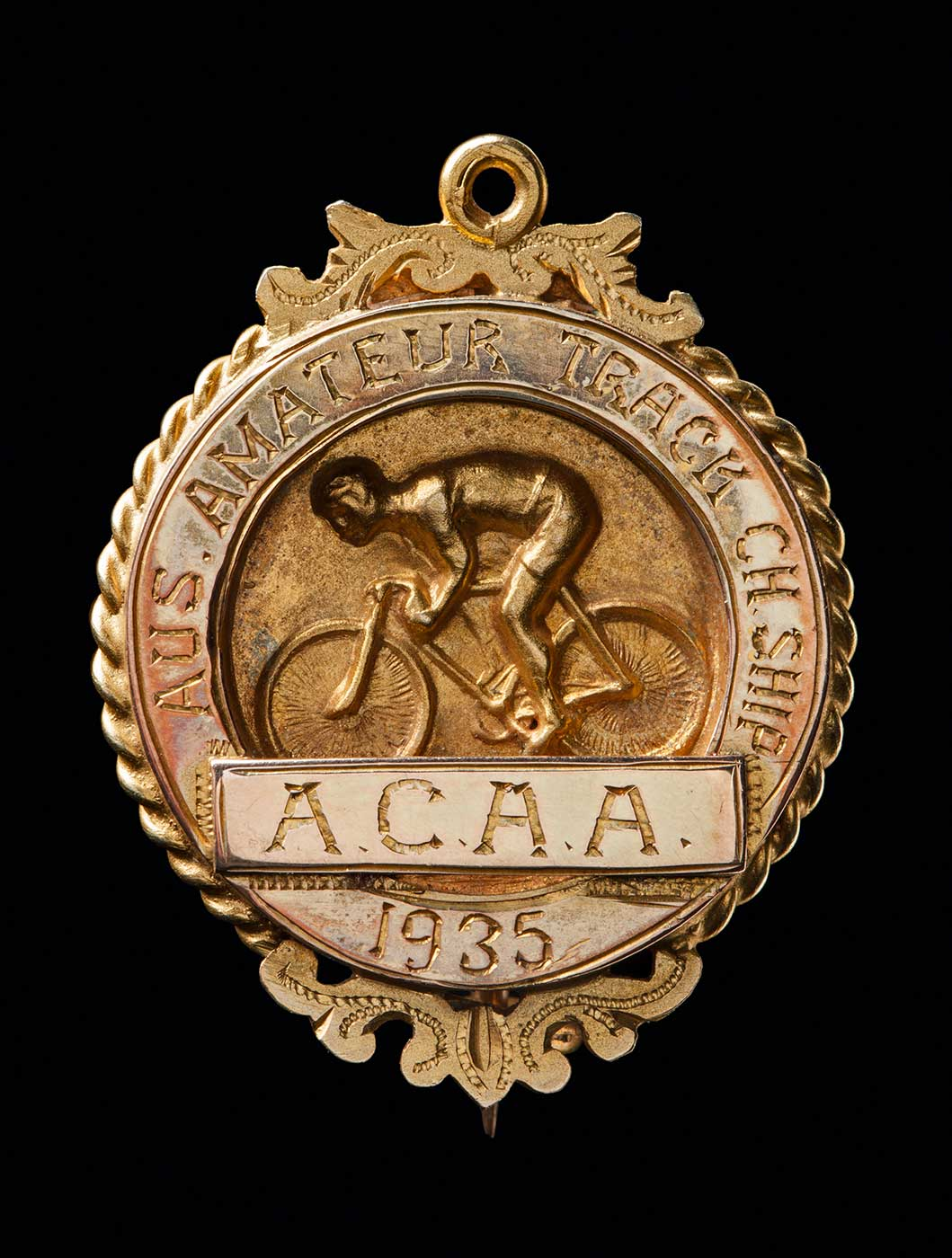 A circular gold-plated medal with a pin clasp. The medal is decorated on the front with a raised relief of a cyclist with inscriptions that read 'AUS AMATEUR TRACK CH.SHIP / ACAA / 1935'. Also inscribed on the reverse side of the medal is '10MILE / CH. / R. GOODWIN / 2ND'. - click to view larger image