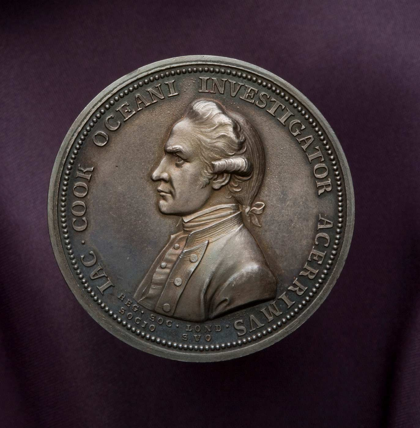A solid copper medal with a bronzed patina, which features on the obverse a profile portrait bust of Captain James Cook in uniform, and on the reverse Fortune leaning upon a column with a spear in the crook of her arm, holding a rudder on a globe. Encircling the portrait of Cook is the Latin text