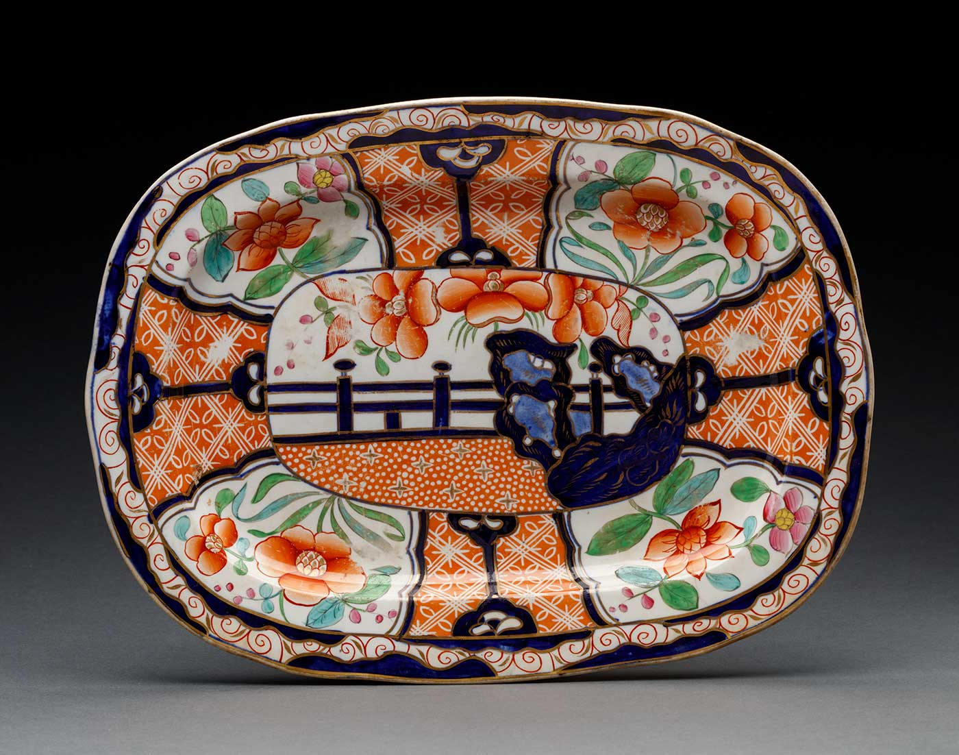 A rounded rectangular platter featuring an orange, white, blue, pink, green, yellow, and gold floral design. - click to view larger image