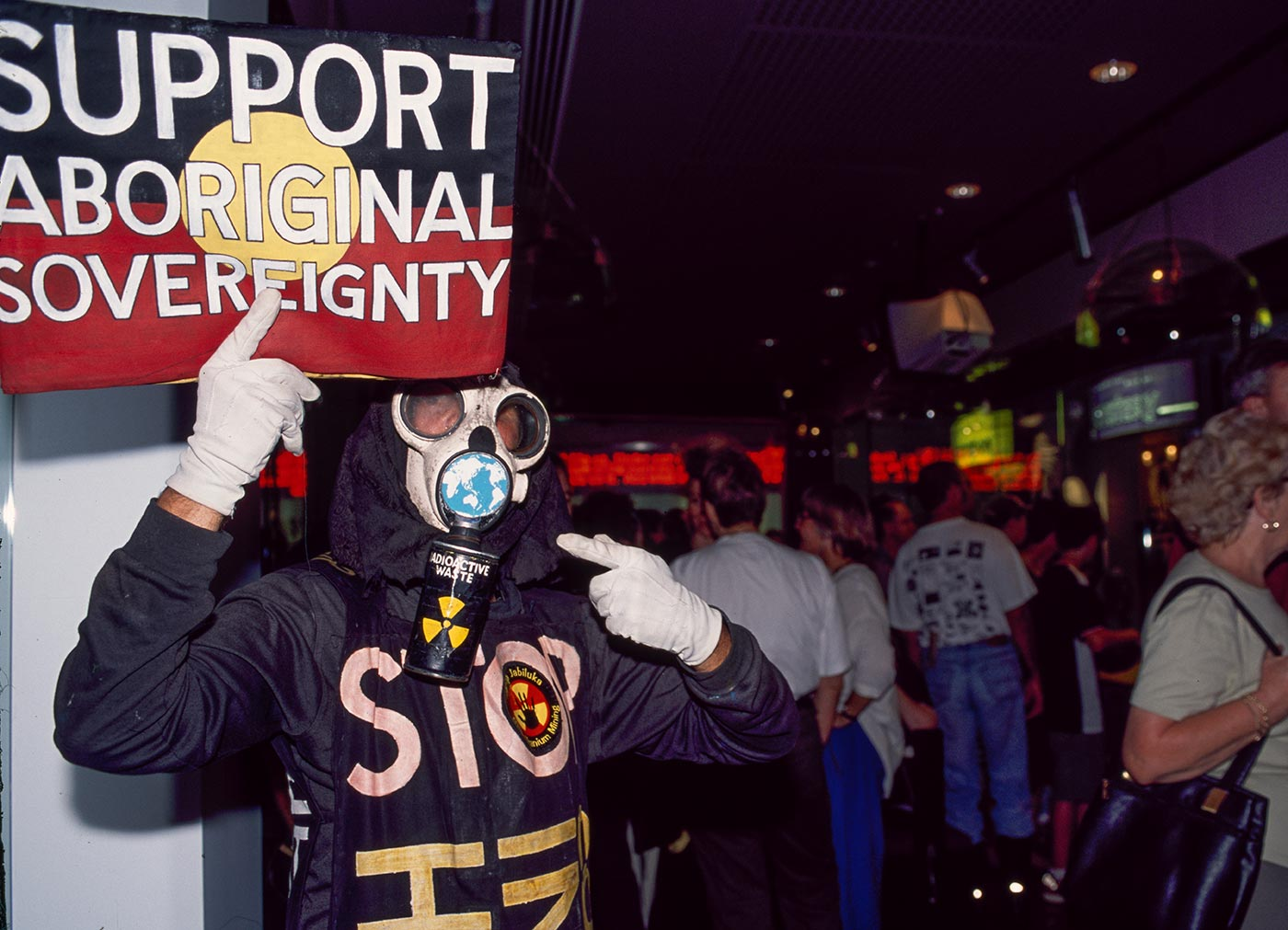 Man wearing a gas mask and clothing displaying words of protest - click to view larger image