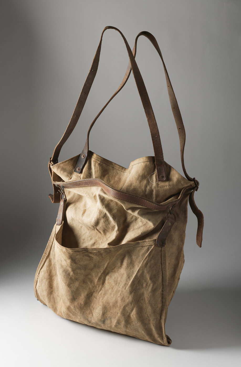 A canvas fruit picking apron featuring leather straps with metal buckles. The canvas of the apron is white but has discoloured from use. The front section is slightly higher than the back section and the top front corners of the apron are folded into triangles to provide the leather straps with an anchor point. One strap is attached from the top of the aprons proper left to the proper right side and the other is attached from the proper right top to the proper left side. A leather strap runs along the back top edge of the apron finishing under each arm of apron. - click to view larger image