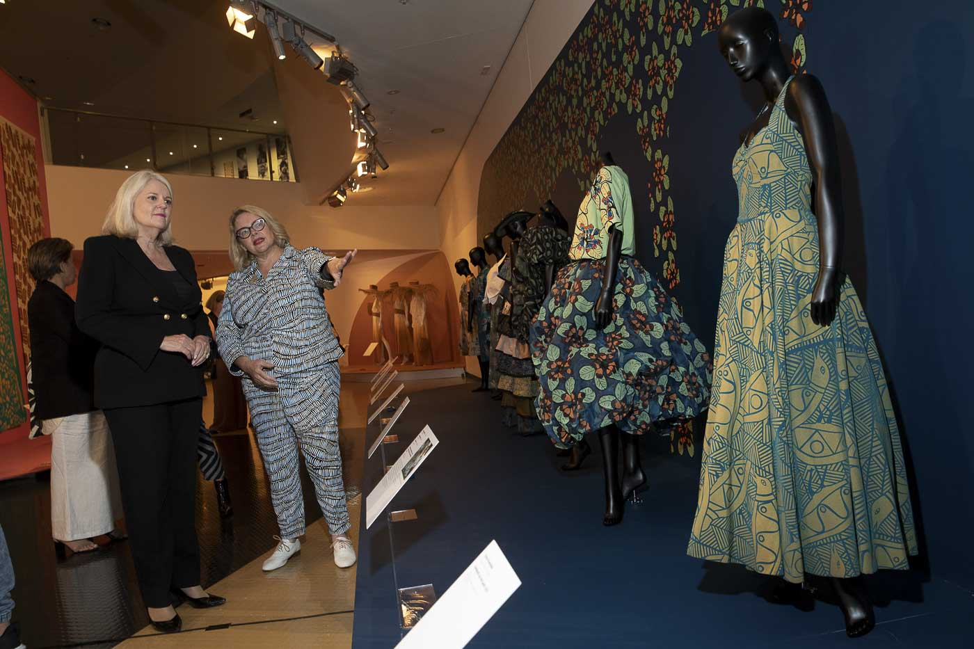 Two women discuss colourful fashion clothing displayed on mannequins in an exhibition space. - click to view larger image