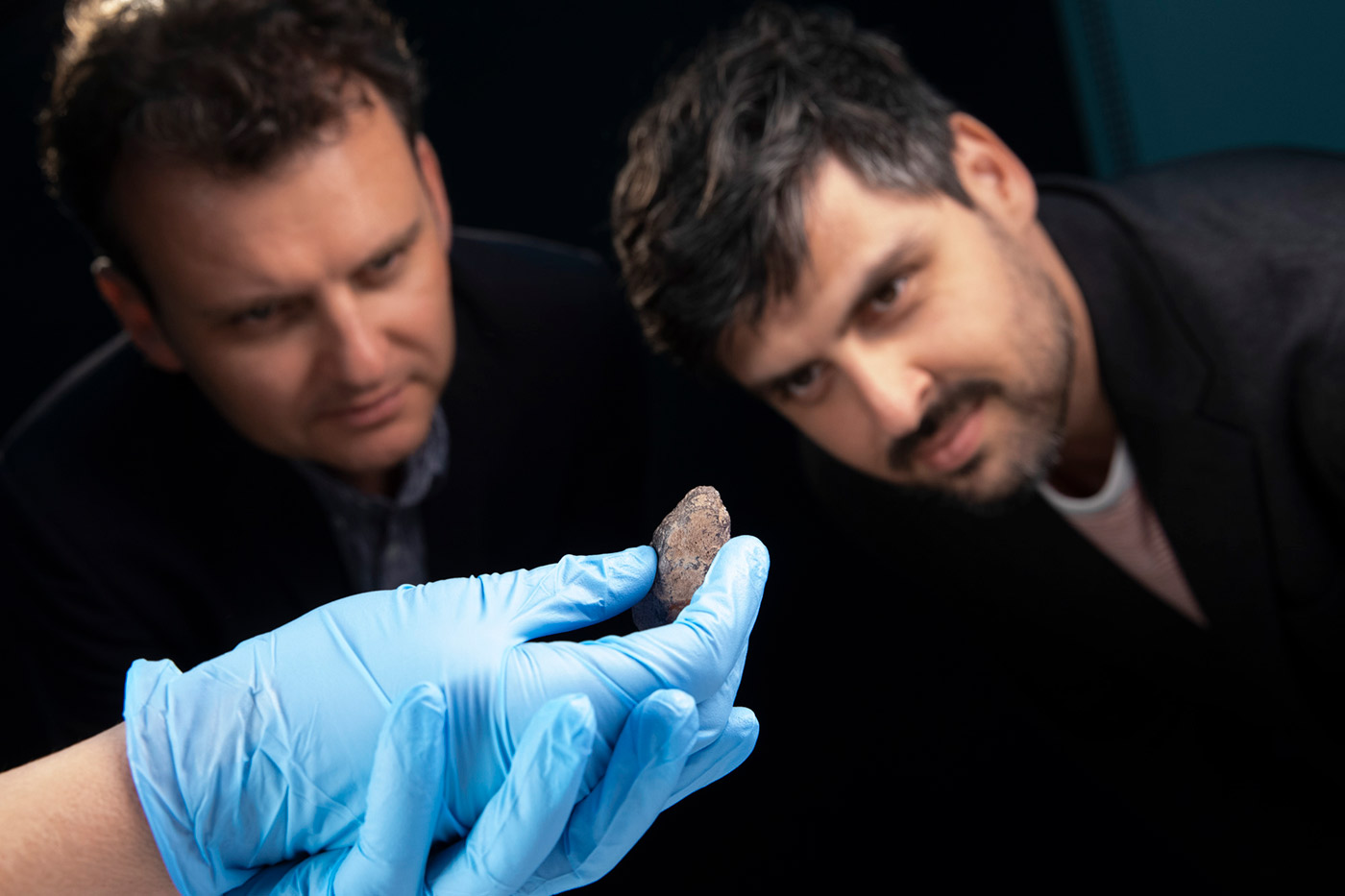 Slava and Leonard Grigoryan inspect a small piece of ochre being held in hand wearing conservation gloves.