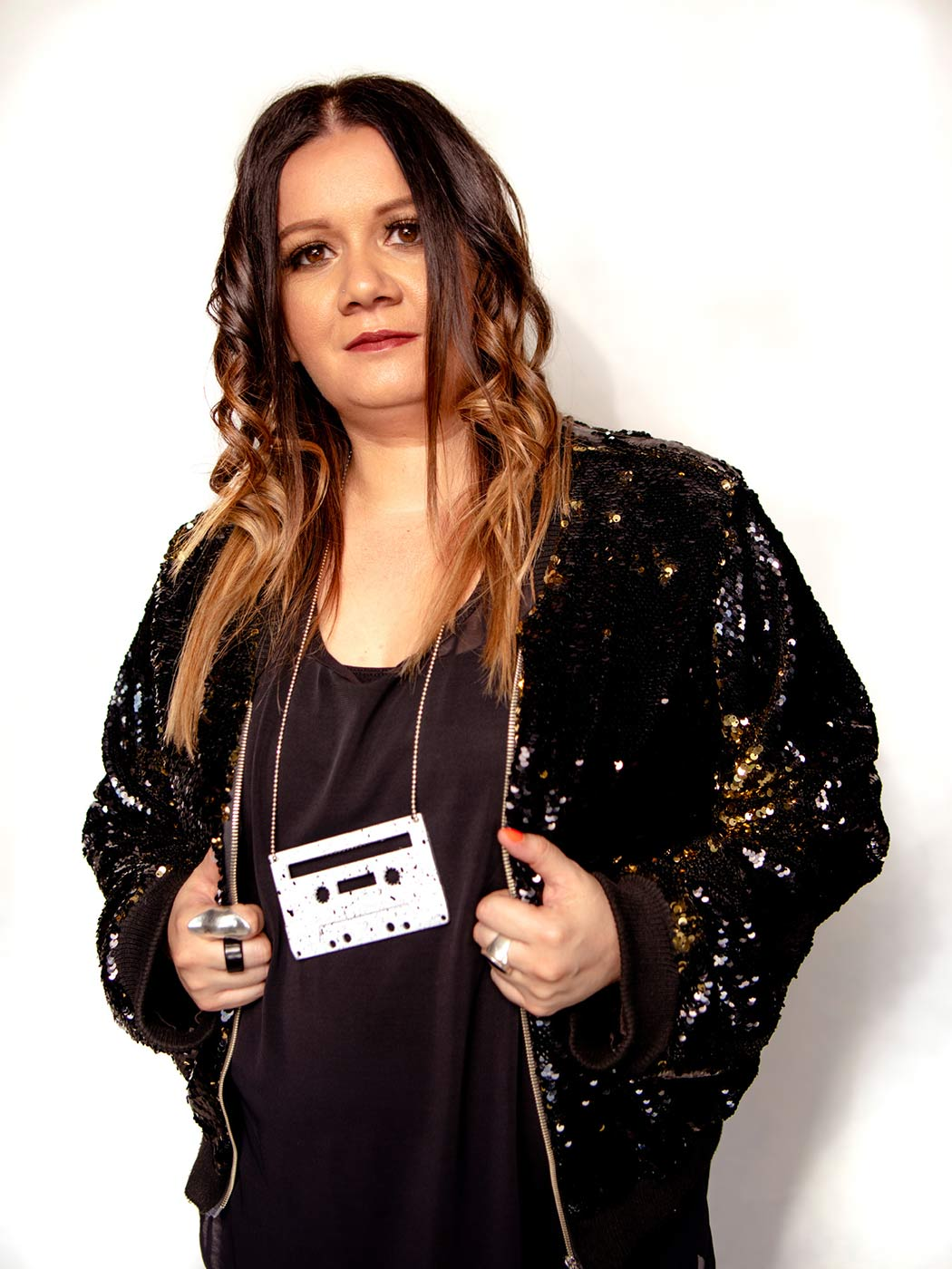 Portrait of a woman wearing a sequinned jacket and a necklace made from a cassette tape. - click to view larger image
