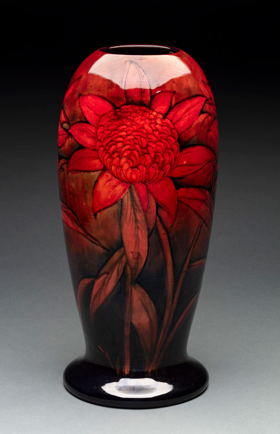 A vase featuring a rich flambe glaze and decorated with red waratahs. The exterior is painted in shades of red, black and blue, and the interior is dark red in colour. Cracking can be seen underneath the glase and there are also a few faults. - click to view larger image