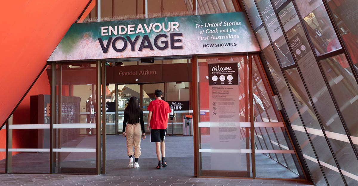 Two visitors walking through a large entrance with a promotional banner for the Endeavour Voyage exhibition above.
