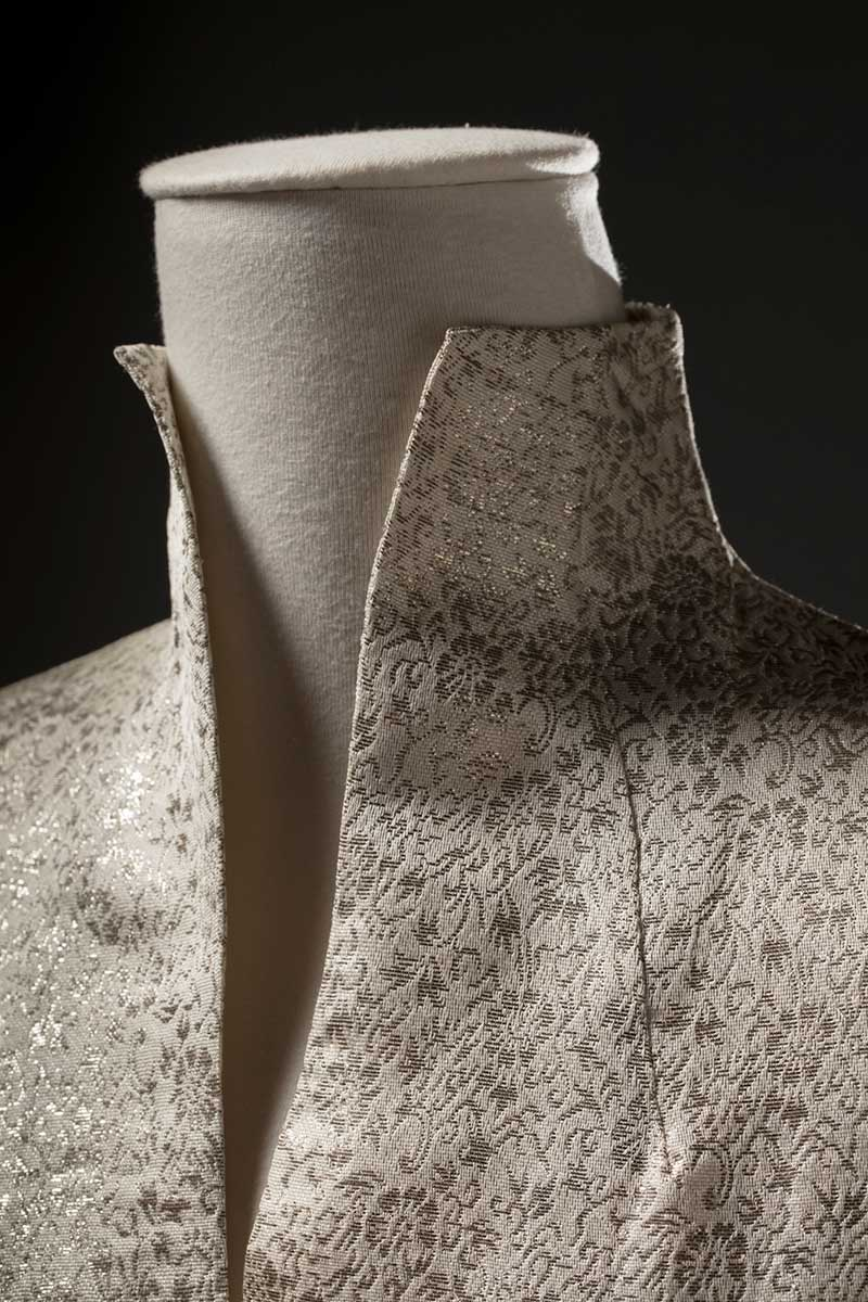 Cropped image of a cream-coloured synthetic brocade dress showing the front neckline area. - click to view larger image