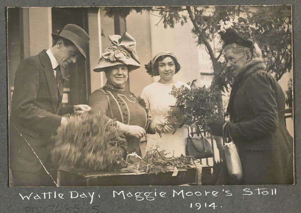 Photograph mounted on board, showing three women and a man standing in front of table loaded with wattle sprays. 'Wattle Day. Maggie Moore's Stall 1914' is handwritten across the bottom of the board. - click to view larger image