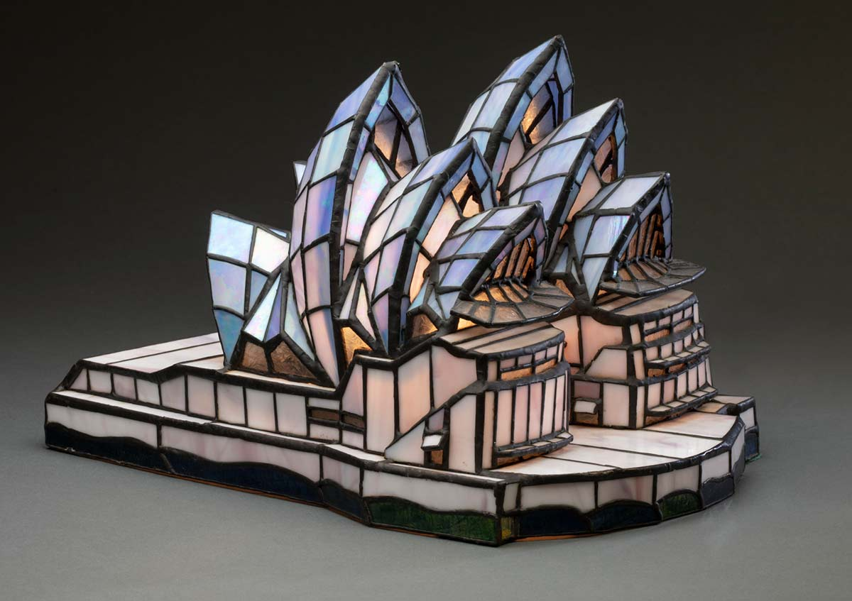A leadlight lamp in the shape of the Sydney Opera House. The glass is white, purple, blue, green and clear in colour, and it is joined together with black metal. - click to view larger image