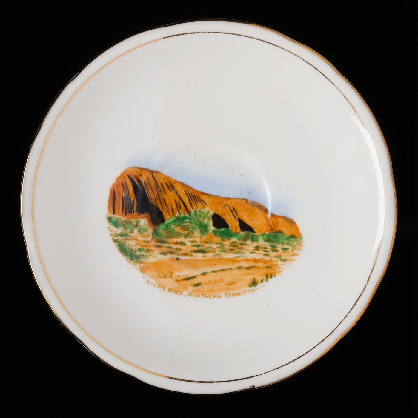 China plate with a gold rim and a painted image of Uluru in the centre. - click to view larger image