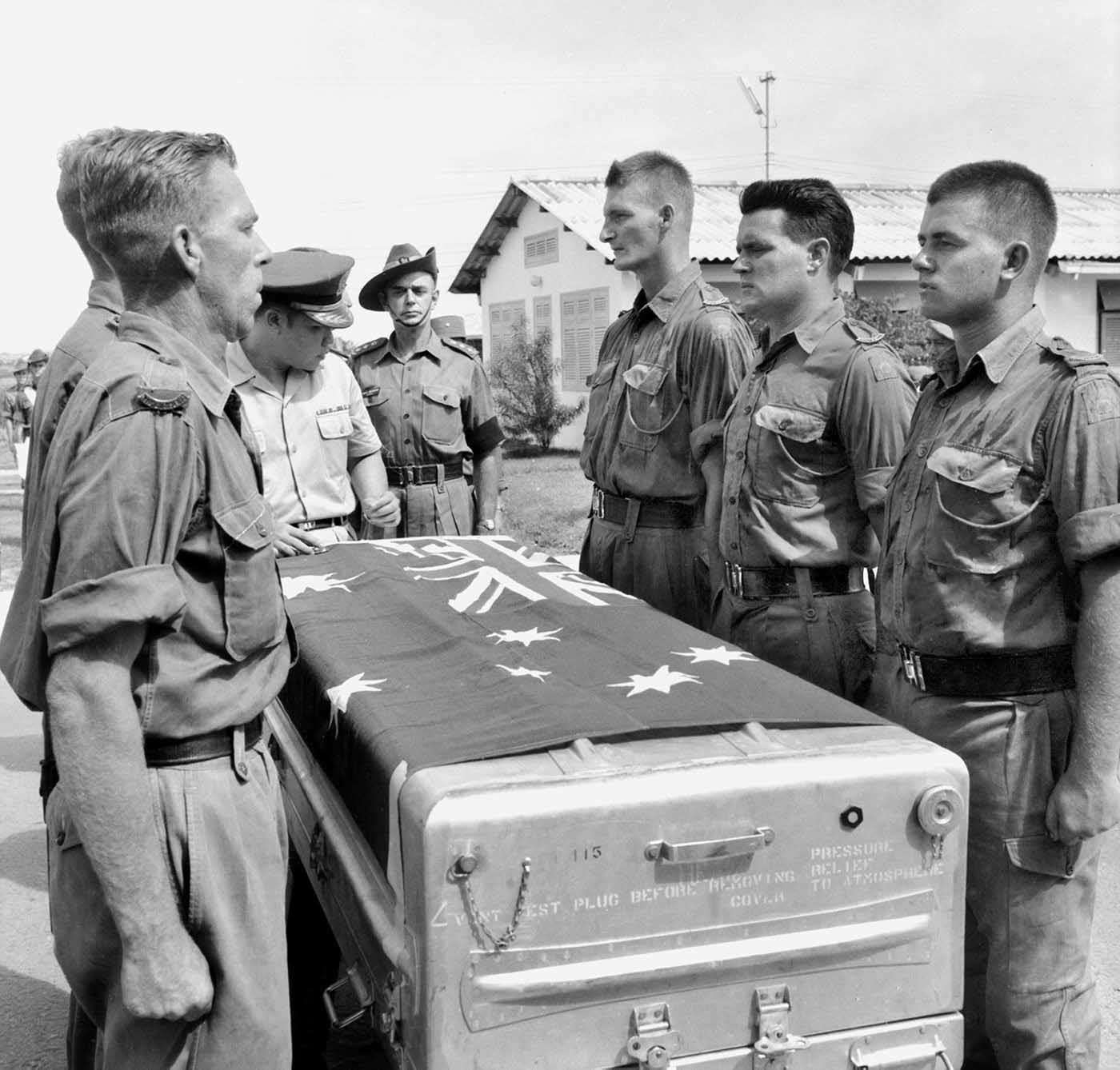A black and white photograph of Australian soldiers in Saigon, Vietnam. They are standing at attention around a metal trunk which has an Australian flag draped over its top. - click to view larger image