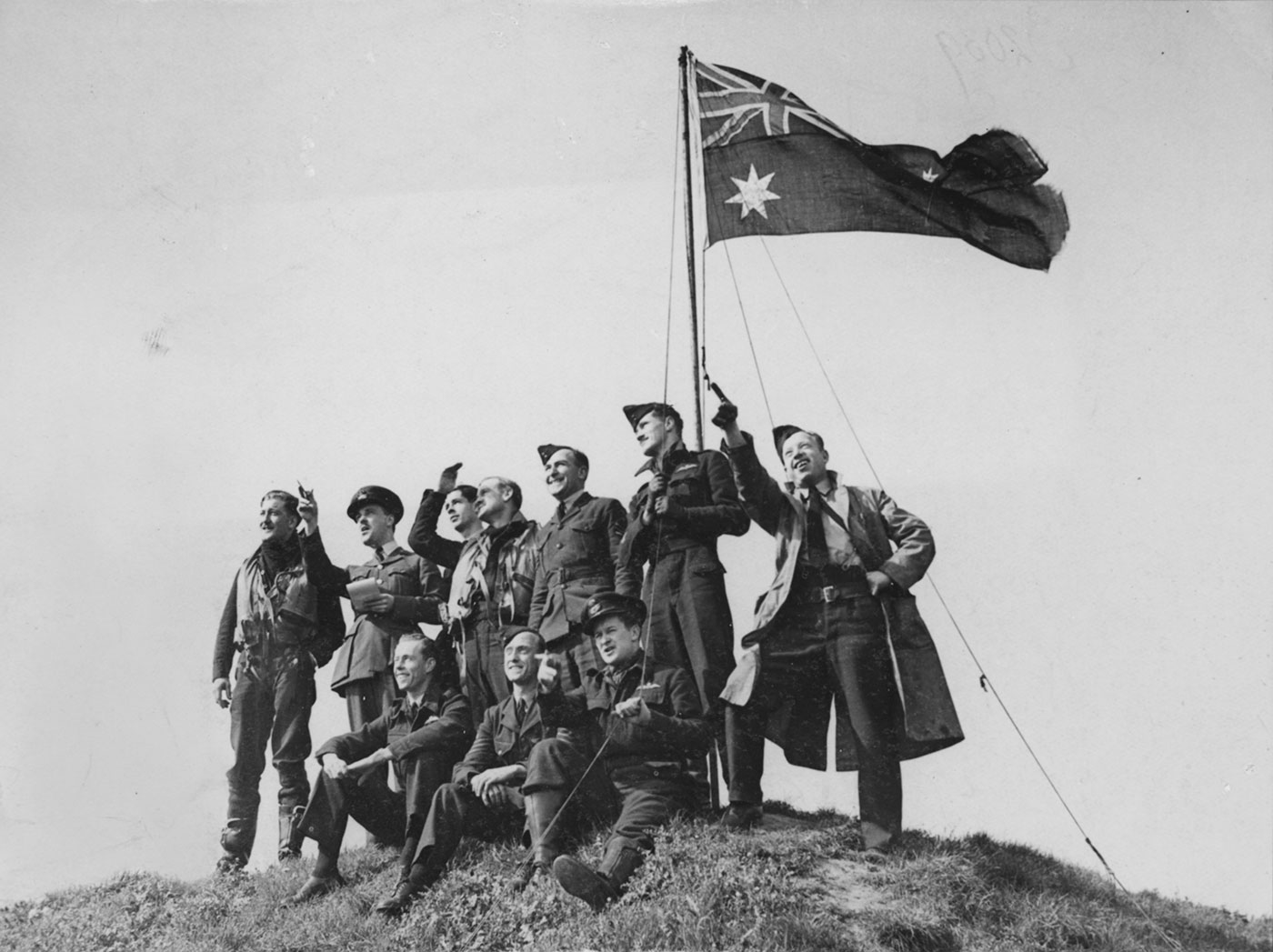 A black and white photograph of an Australian fighter squadron gathered around a raised Australian flag. The men are atop a mound and looking off the left of the photo. - click to view larger image