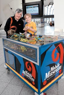 Volunteer Pat Keneally and young Museum visitor Scott exploring a Museum touch trolley.