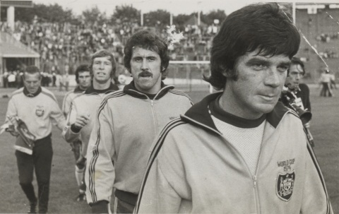 Black and white photograph showing five men walking on a grass field. The man at front right is wearing a tracksuit top with the Australian coat of arms on the right breast and the words 'World Cup 1974' embroidered above. Behind him are four other three other men wearing tracksuit tops. A partially obscured man carrying a camera is visible on the right and crowds of people in tiered seating are in the background.