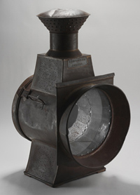 Black-coloured lamp with light metallic casing and circular glass panel at the front.