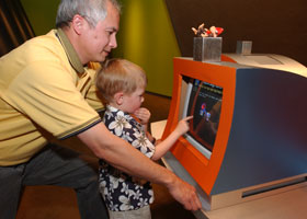 A man and child looking at a computer screen.