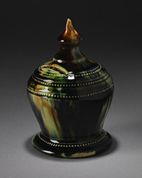 Dark green glazed, vase shaped ceramic money box with a circular base and spherical middle, tapeing to a cone-shaped knob.