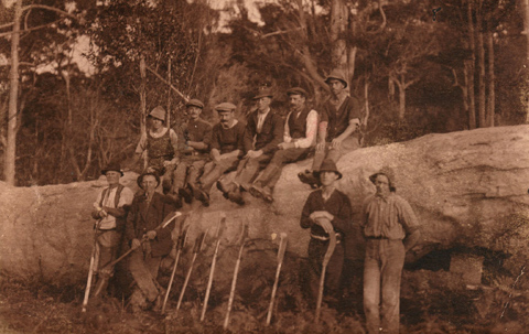 Sepia image showing six men sitting on a felled tree trunk, with four group settlers standing in front. Tools including axes and scrub cutters are propped against the tree.
