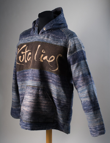 A man's fleecy hooded jumper made from resist-dyed woven cotton fabric of mixed streaks of blue, light blue, black, grey and white. A panel of black fabric at chest-height on the front of the jumper shows the name 'Kuta Lines' in yellow hand-written-style script.
