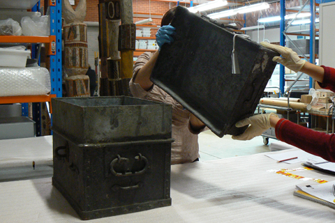Conservation staff remove the lid from the bullion box's protective case.