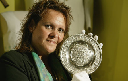 Evonne Goolagong Cawley, wearing white cotton gloves, holds a small silver plate.