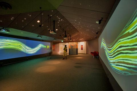 Image of a woman standing in the welcome space of the First Australians gallery. The Seven Sisters constellation lighting installation is visible in the ceiling.