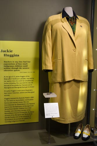 Display featuring the yellow outfit worn by Jackie Huggins