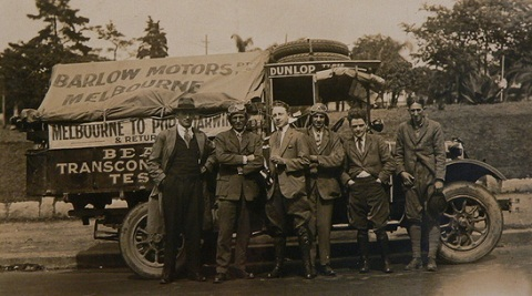 Black and white image showing six men standing in front of a truck which has a canvas cover at the back bearing the words 'BARLOW MOTORS / Melbourne'. All the men wear suits. Those standing second and fourth from left also wear leather flying-style caps and goggles on their heads.