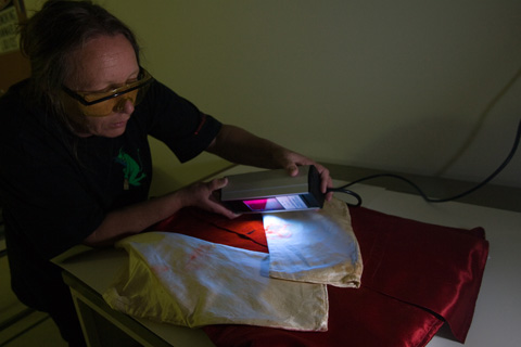 Conservator Deb Spoehr uses ultraviolet light to investigate staining on racing silks worn by the jockeys of Gaulus and the Grafter in 1897 and 1898 Melbourne Cup races.