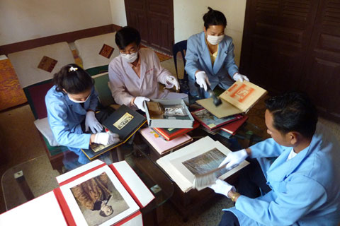 Staff from Collections and Exhibitions section examining for pests and cleaning photographic archive material in preparation to rehouse the collection.