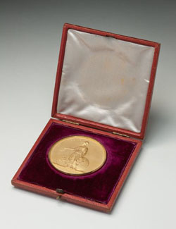 A gold medal in a presentation box. The medal shows an image of a woman holding a wreath and a scroll, with the text 'OB TERRAS RECLUSAS / ROYAL GEOGRAPHICAL SOCIETY OF LONDON'. The case is lined purple velvet, and white satin on the lid.