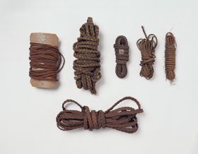 Plaited bands of varying thickness made of coconut fibres, and other plants. Some wrapped around old playing cards.
