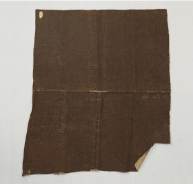 Thick barkcloth that consists of two different pieces pasted together. One piece is brown and the other white.