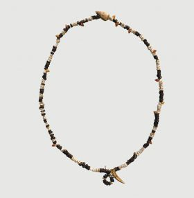 Necklace consisting of flat white shells, brown wooden discs, small red snail shells, one larger snail shell, and one tooth arranged on string.