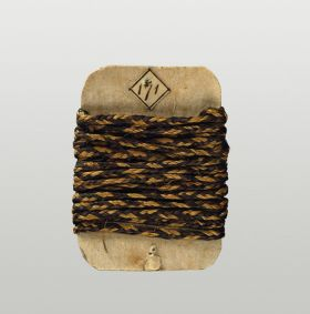 Cord made of plaited flax, yellow and brownish-black, and wrapped around a card.
