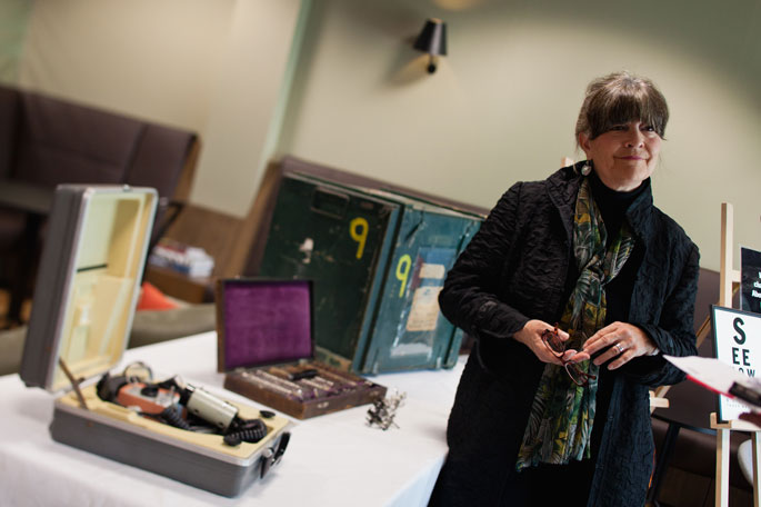 Gabi Hollows stands at right, beside a table where several cases of equipment are displayed.