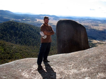 A man standing on a large rock at altitude. A large expanse of bush can be seen in the background.