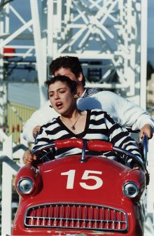 A woman sits at the front of a red rollercoaster car, with another person partially visible in the seat behind.