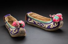 Colour photograph of two embroidered slipper-style shoes with upturned toes and pink and green pompoms at the end.