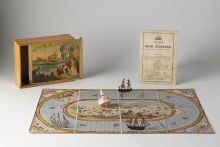 A playing board with three sailing ship markers and a dice, in front of a box with 'RACE TO THE GOLD DIGGINGS' printed on the sliding lid, and a printed rule sheet.