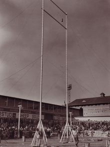 Black and white photograph showing a crowd of people looking skyward at a small wheatbag which has been flung high into the air, between two vertical poles.