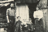Black and white photograph showing a settler family outside a slab hut.