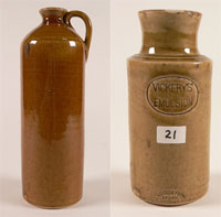 Two tall cylindrical honey brown glazed vessels. On the left is a jug with straight sides tapering to narrow neck and a single handle attached at neck and shoulder. On the right is a jar with a rounded base and straight sides, tapering in to the neck then flaring at the lip. Stamped into one side is the text 'VICKERYS' EMULSION' in an oval frame. Stamped just above the base is the text 'THE BENDIGO POTTERY / EPSOM / BENDIGO' also in an oval frame. A white sticker with '21' handwritten in black appears between the two stamps.
