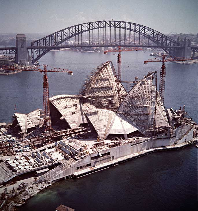The almost completed Opera House in foreground surrounded by cranes, with Harbour Bridge in background.